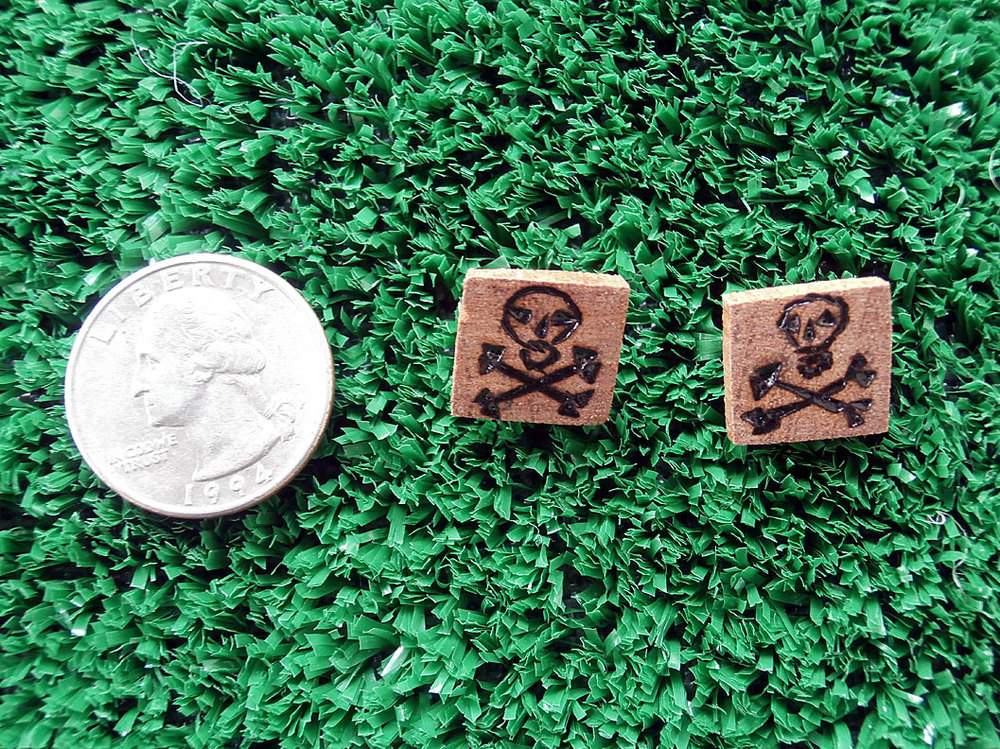 Mahogany post earrings with skull and cross bones.