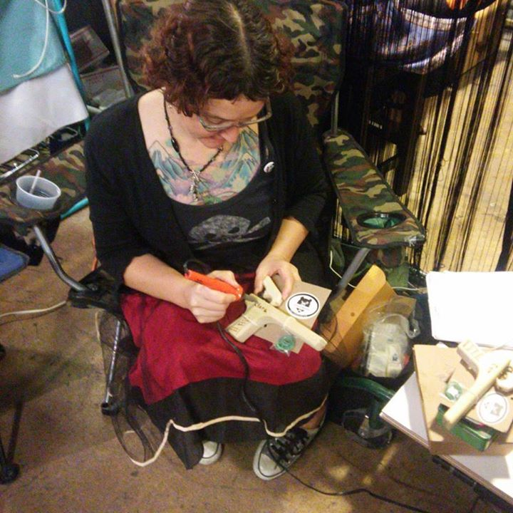 Sarah custom wood burning kids names on a pair of brother and sister rubber band guns at the Summer Show ATX