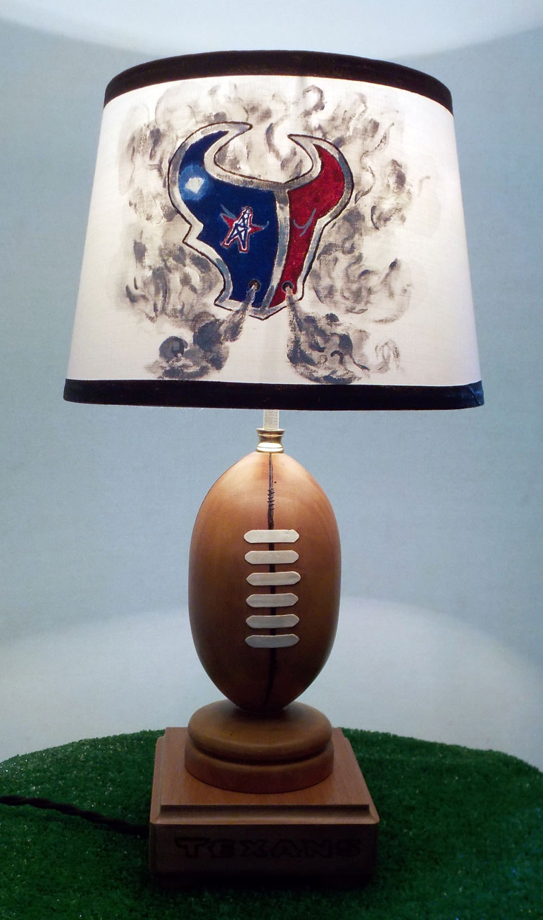 Check it out Texans fans, the ultimate football lamp! Mahogany wood turned to a football shape set on a wood burnt base with hand painted shade.With the light on, the hand painted Texans logo motif comes to life.