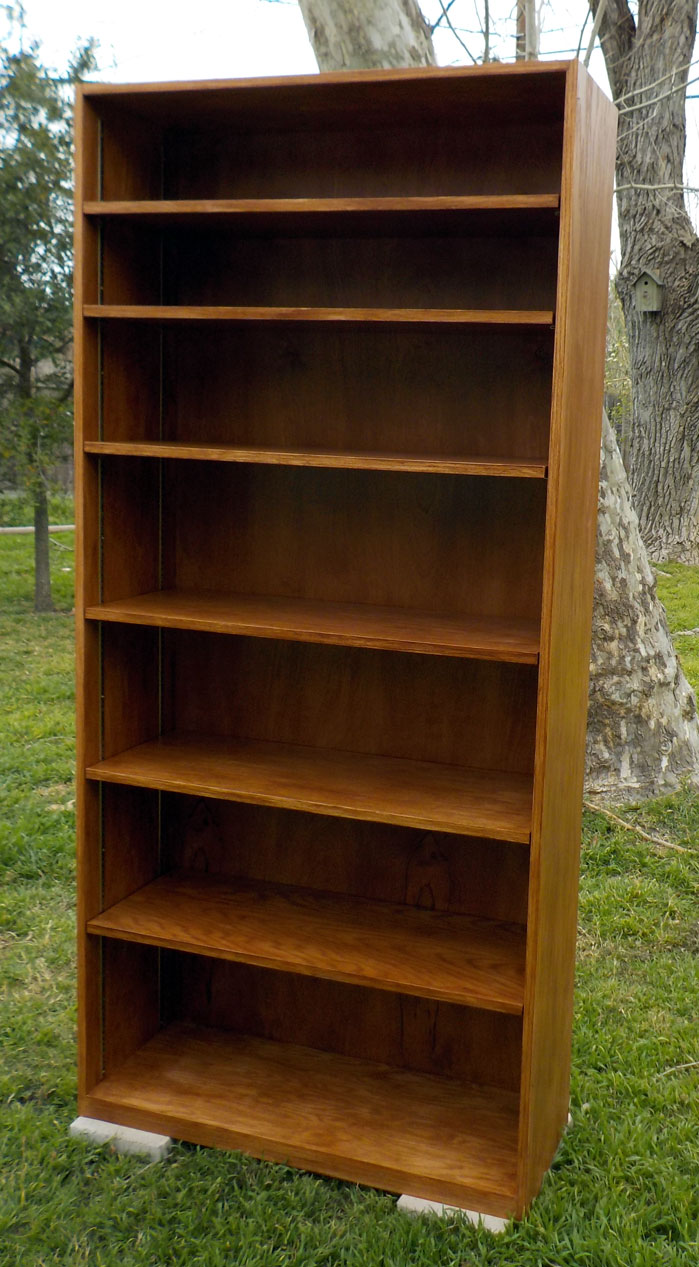 Super sturdy bookshelf made of red oak plywood, hand banded with red oak banding, stained with antique walnut, and brass shelf standards.