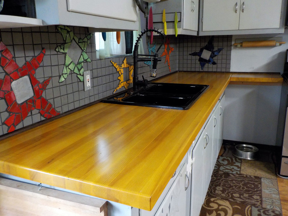 Maple stained with a diluted amber dye stain highlights the yellow mosaic star in the back splash.