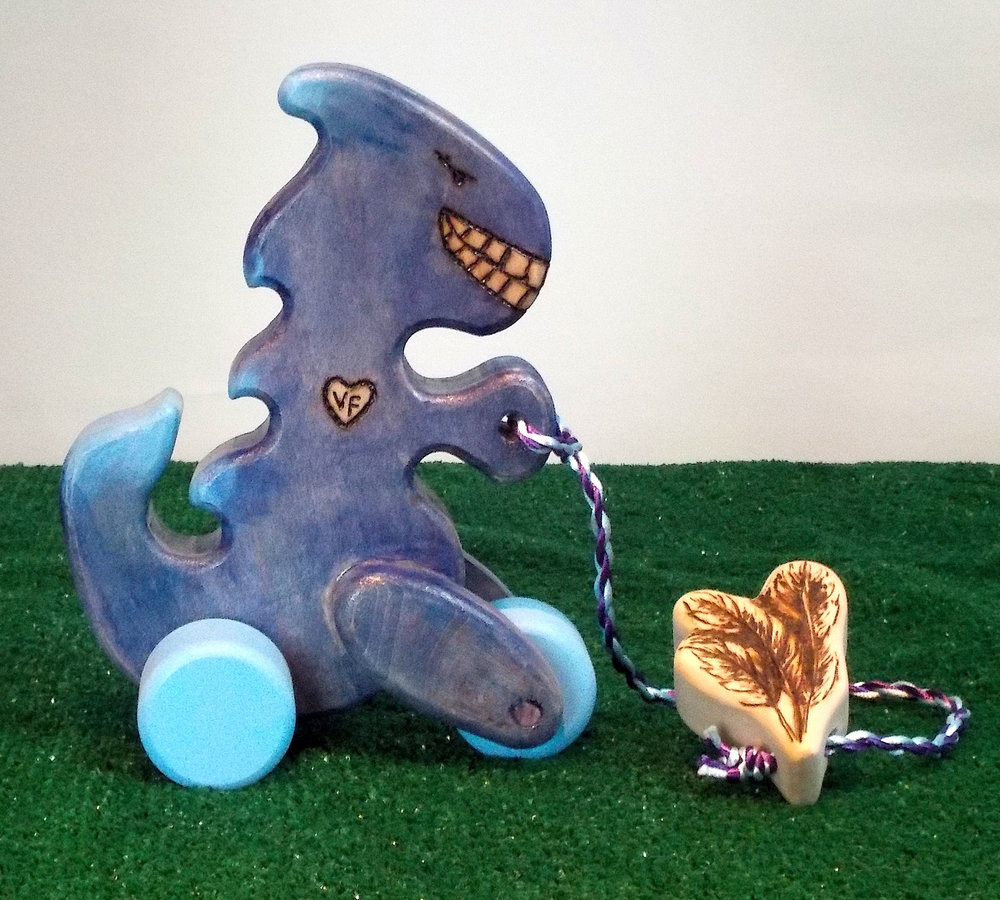 Baby Van Feather's has arrived! In celebration, for the baby shower, we've created this cute little purple pull dino with feather's wood burnt on the teether handle.