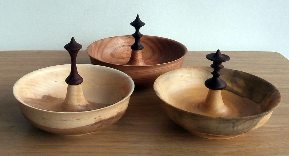 Three unique bowls with decorative finial in the center.