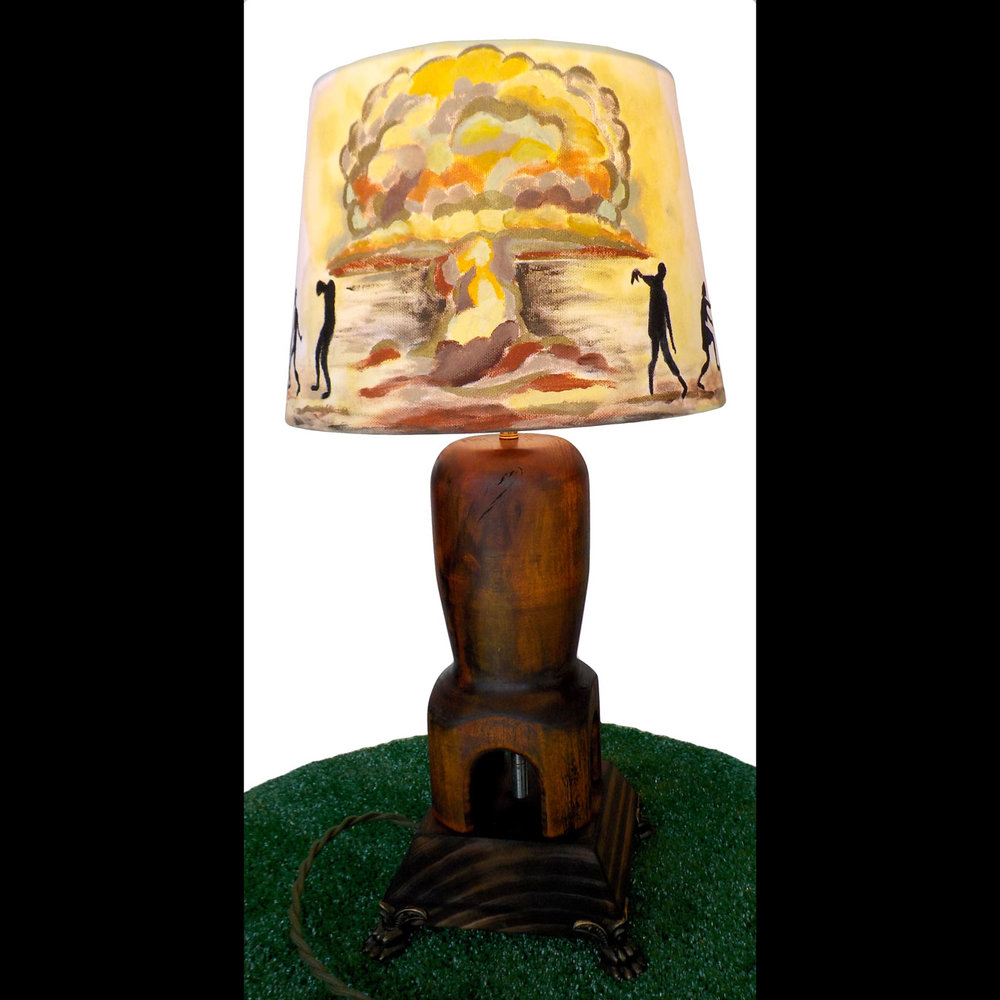 Painted with zombie shadows emerging from a nuclear blast explosion. The base is made of Poplar wood turned on the lathe to look like a bomb and stained with a variety of colors in layers to make an antique finish. The lamp base is poplar wood burnt with a torch and is mounted on brass claw feet corners.