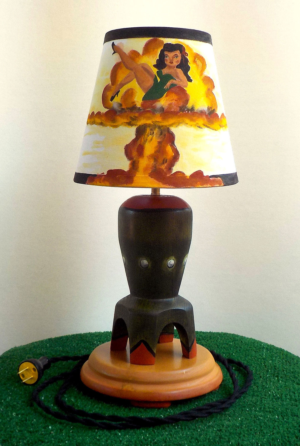 Painted shade with a bombshell pinup girl in a nuclear blast explosion. The base is made of Poplar wood turned on the lathe in the shape of a bomb and hand stained and painted.