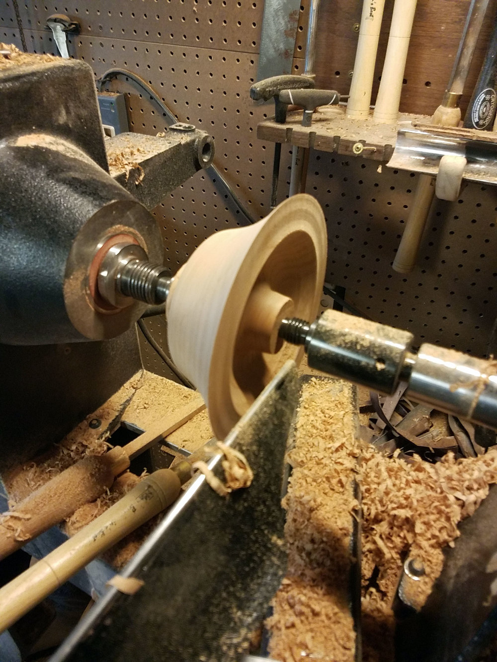 At one point, the chunk of Cherry wood is turned between centers on the lathe.