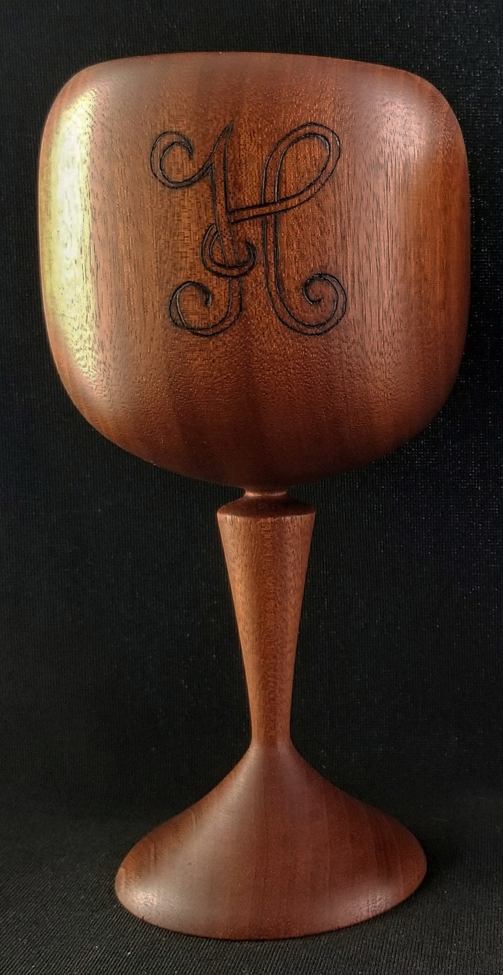 Mahogany wood wine goblet with the letter H in classic wedding font inscribed on it.
