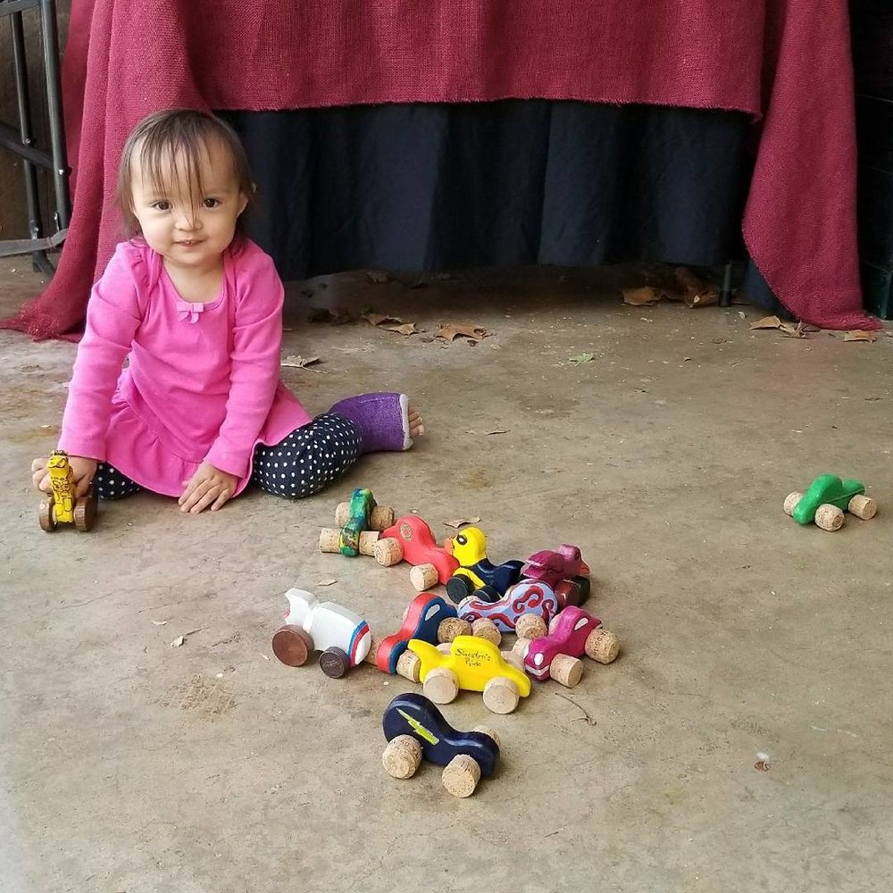 The cutest kiddo test driving all of the Chaos Woods wooden cork cars!