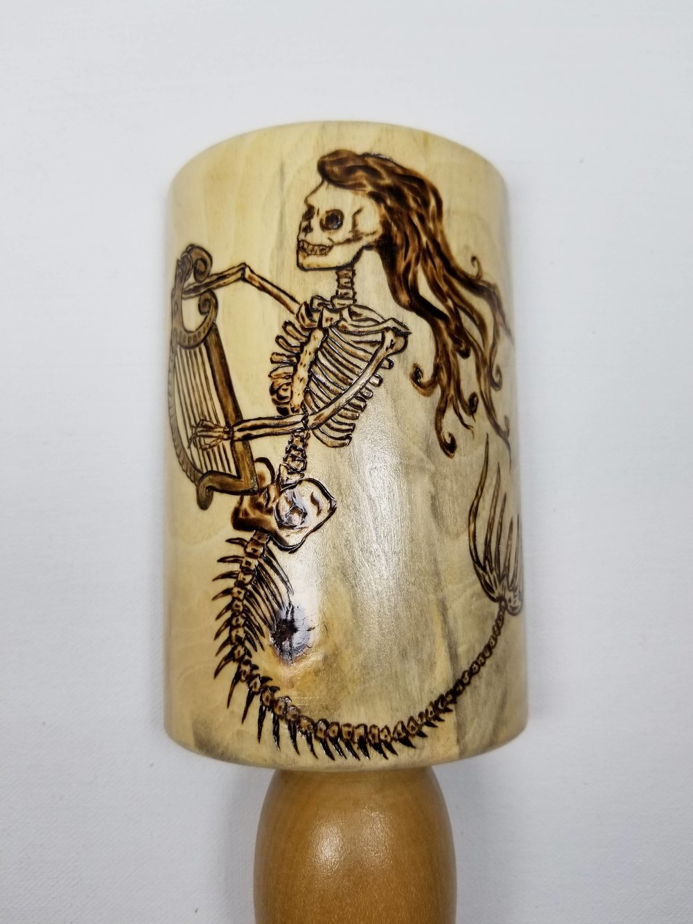 Skeleton banshee mermaid on a bar tap handle.