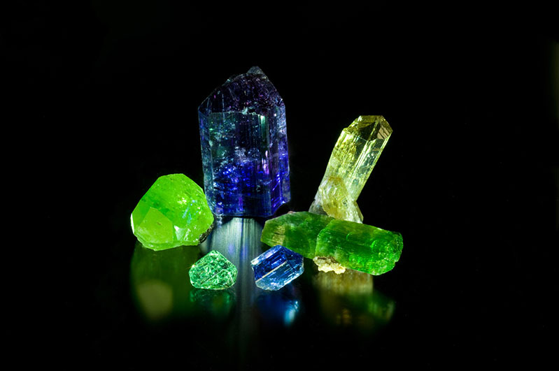 Merelani mix. Clockwise from top center: tanzanite 5.5 x 2.7 cm., yellow zoisite 4.6 x 1.5 cm., tremolite 5.1 x 1.8 cm., tanzanite 1.7 x 1.1 cm., grossular garnet 0.9 x 1.4 cm, diopside 3 x 2.5 cm. From the collection of William Larson.