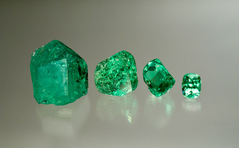 Fine group of mint-green grossular rough. Merelani, Tanzania, with a cut gem of 7+ carats.