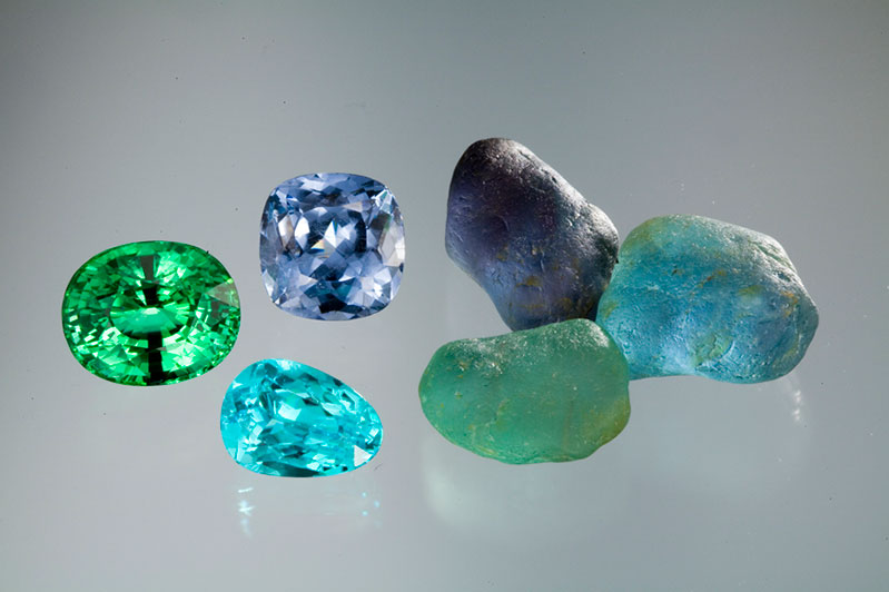 Gem quality nodules of copper-bearing tourmaline from Mozambique. Amongst the cut stones, the largest is 15+ carats. The 8-carat pear cut is the favored Paraiba color.