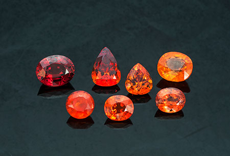 Spessartite Suite: (l–r from top row) 24.80-carat oval from Nigeria (Inv. #13832), 17.71-carat pear shape from Nigeria (#20423), 12.90-carat pear shape from Nigeria (#16043), 22.73-carat cushion from Tanzania (#21599), 12.71-carat round from Namibia (#1531), 10.46-carat oval from Tanzania (#21598), and 11.10-carat oval from Nigeria (#21569). Click to enlarge. (Photo: Mia Dixon)