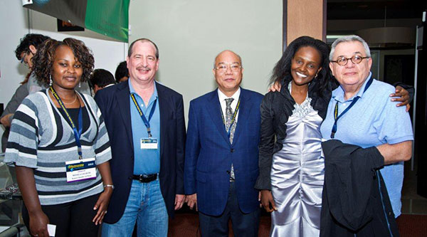 Delegates and exhibitors  paused for a photo at the Arusha International Gem and Mineral Fair. From left, Monica Gichuhi CEO of the Kenya Chamber of Mines; gem dealer Evan Caplan; President of the International Colored Gemstone Association, Wilson Yuen; gem dealer Miriam Kamau; and gem dealer Benjamin Hackman. (Photo: Robert Weldon, © GIA 2012)