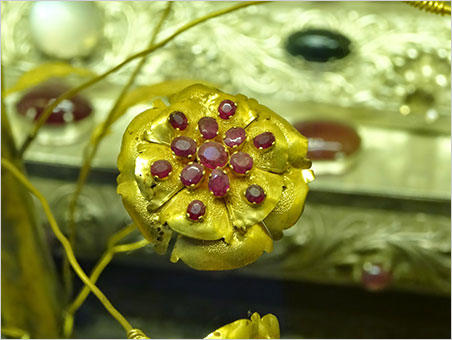 Posy. A jeweled flower composed of gold and rubies. It decorates the base of one of a pair of statues of the Buddha on which devotees apply gold leaf in Mogok's largest pagoda. Not surprisingly, the Buddha images have been removed from the valuable bases, which now are in a vaulted case. (Photo: Eloïse Gaillou © NHMLAC)