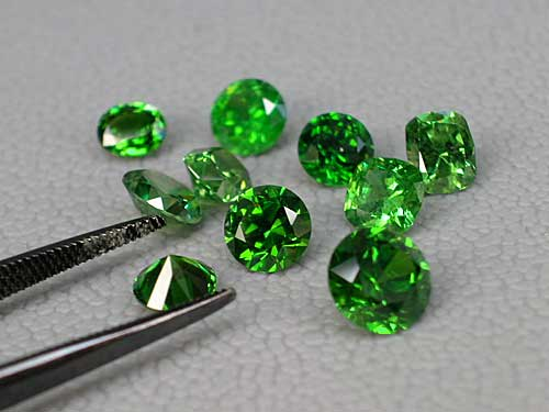 This suite of 0.75–2.0 ct. demantoid garnets shows the typical range of colors possible. The ideal body color would be the center stone, which is not too light or dark, but the lighter tones show off demantoid's fire to better effect. (Photo: Wimon Manorotkul; Gems: Pala International)