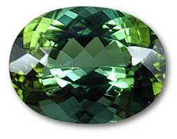 The effects of pleochroism can clearly be seen in this oval green tourmaline. Along the vertical axis, a bluish green color is seen, while along the horizontal axis, the color is yellowish green. This is a product of the doubly refractive nature of tourmaline. Photo: Wimon Manorotkul