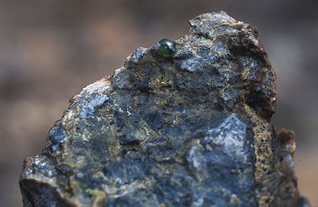 Peek-a-boo.  A green demantoid emerges from its matrix. From the Kladovka Mine, 2004. (Photo: Bill Larson)