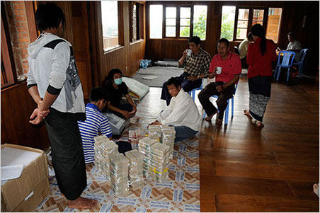 Lots of kyats.  A successful auction had taken place during Pala International's Bill Larson's  2013 visit  to Burma. Note the automated money counter (next to masked man). The bid was 700 million kyats in a country where the largest bills are 10 thousand. That's at least 7,000 bills to count! ~950 kyat = $1.00. This image illustrates why some people would prefer trade in dollars. (Photo: Bill Larson)
