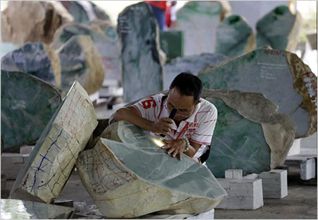 A merchant inspects a jade boulder at the emporium, June 24, 2015. See a brief streaming video about Hpakant jade mining produced by Democratic Voice of Burma. DVB produced a video in the same series that profiles the artisan workshops of Mandalay.