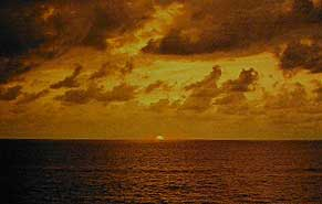 Figure 4. A sunset on the coast of Sri Lanka at Colombo, November, 1988. One can clearly see the strong yellow-orange presence in the direct sunlight. This results from greater scattering of blue-violet wavelengths as the path length of sunlight through the earth's atmosphere increases towards sundown. It is evident that the use of direct sunlight (as opposed to skylight) just after sunrise or before sundown could definitely enhance the appearance of yellow, orange and red stones. Photo:  Richard W. Hughes .