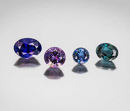 Spring quartet.Left to right, a Burmese 3.39-carat spinel (#18978), a Sri Lankan round purple spinel weighing 2.94 carats (#20775), followed by a blue round Ceylon spinel weighing 1.36 carats (#21745) and lastly we have a blue-green color-change Sri Lankan spinel weighing 2.20 carats (#21746).Clickto enlarge. (Photo: Mia Dixon)