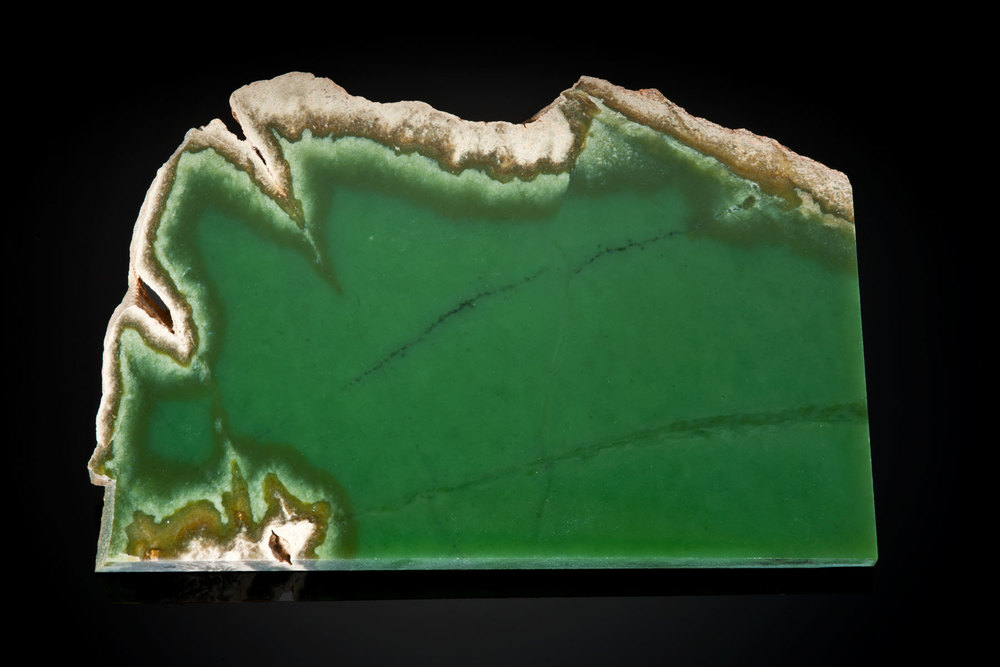 "The light tan rind often hides the beautiful green jade in this 7"" x 3½"" x ¼"" slice. Most buyers prefer the non-included, pure translucent green rather than this attractive slice and will pay dearly for such jade.  (Photo: Robert Weldon)"