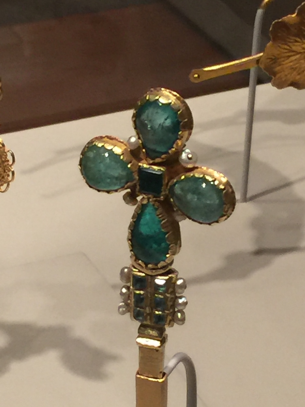 Cross finial, Colombia or Ecuador, circa 1600. Gold, emeralds, pearls. Denver Art Museum, Gift of the Stapleton Foundation of Latin American Colonial Art made possible by the Renchard family; 1990.526.