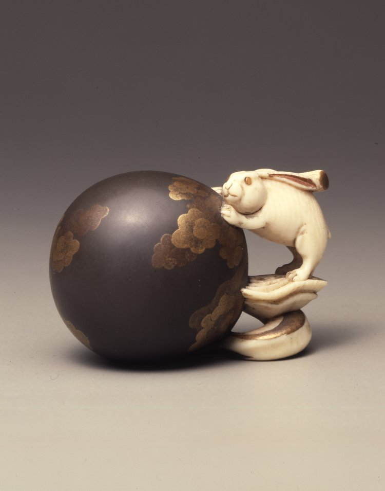 A whole world.  Netsuke, hare with pestle and globe, lacquered ivory, 4.4 cm. Bequeathed by Anne Hull Grundy. (Photo © The Trustees of the British Museum)