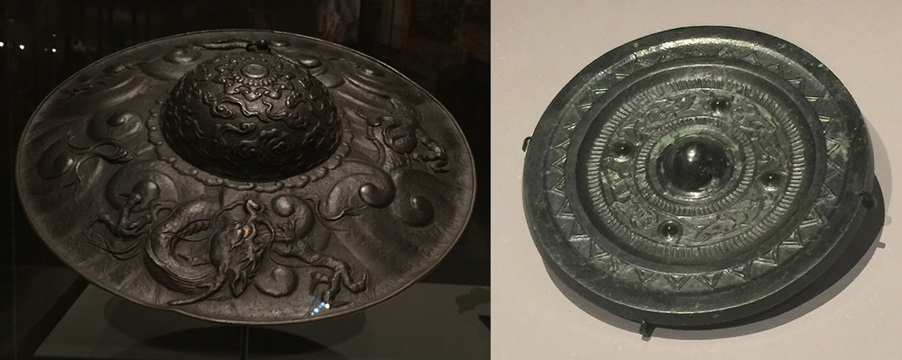 Circles:    Accessoires cabochon.   At left, from  Samurai , a military hat, signed by Myochin Muneakira, mid Edo period, 1700s, iron, gold and copper. ( On another piece he boasted that he was Japan's best armorer.)  The hat's graceful, even delicately detailed dragon with its golden eye ( click  to enlarge) was created using a  repoussé  technique, i.e., hammering the designs in reverse from below. At right, from  Life and Afterlife , a bronze mirror featuring animal figures, of the Han Dynasty (third century B.C.E.–third century C.E.), which also brought Japan its now-traditional robe that we know as kimono. What look to be dark cabochon gemstones actually are part of the bronze material. This is the most ornate piece in  Life and Afterlife , and probably one of the latest in the exhibition. (Photos: David Hughes)