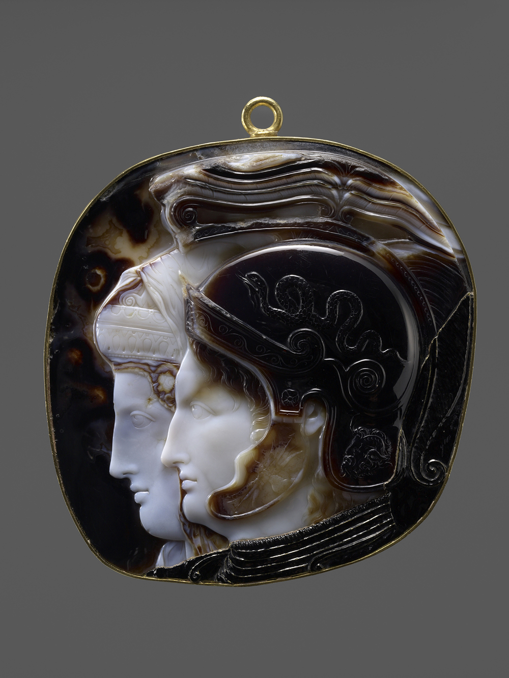 "The Vienna Cameo. Greek (Ptolemaic), Early Hellenistic period, 278-270/69 B.C.E. Ten–layered onyx (Indian sardonyx). H. 41/2 in. (11.5 cm), W. 4 in. (10.2 cm). Antikensammlung, Kunsthistorisches Museum, Vienna (IXa 81). This cameo portrays Ptolemy II Philadelphus in the foreground wearing an Attic helmet whose cheek guard depicts a thunderbolt, an attribute of Zeus. The snake on the dome is the descendant of the Hellenized Egyptian cobra seen on the pharaohs' own war helmets. The neck guard displays a portrait of the Egyptian god Ammon. In the background is the sister wife Arsinoe II, wearing a hood-like crown beneath a veil. These two ""sibling gods"" would have been worshipped in their lifetimes at the shrine of Alexander in the Ptolemaic Kingdom governed in Alexandria."