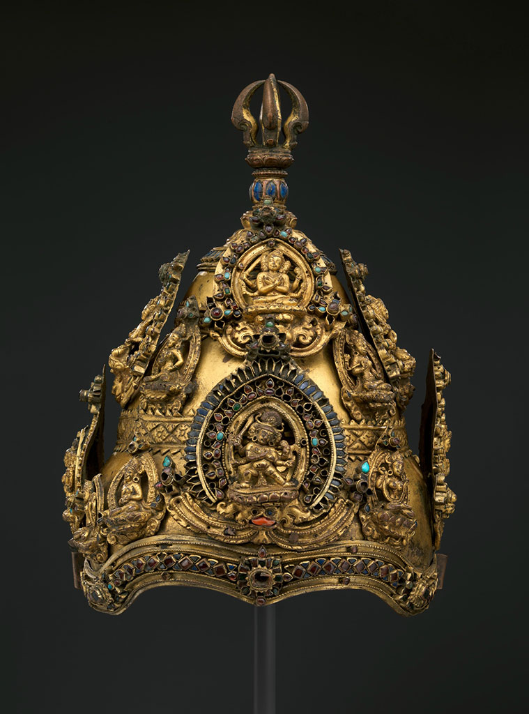 "This rare Nepalese ritual crown has been donated to The Metropolitan Museum of Art by collector Barbara Levy Kipper. The crown features four sets of diadem plaques that depict Manjushri (Gentle Glory), the Bodhisattva of Transcendental Wisdom, in his esoteric form of Manjuvajra (Gentle Thunderbolt)—in both his benign (upper, in the image) and wrathful (lower) guise. Each of these depictions is surrounded with precious and semiprecious gemstones, turquoise, rock crystal, coral and glass. These main plaques are accompanied by smaller depictions of female forms, likely Shakti deities that often are portrayed entwined with the main figure: the union of wisdom and creative power (bliss-emptiness  per  Wikipedia). The Met news release  states  that the image of the wrathful Manujavra is rarely depicted, ""standing in an aggressive posture ( pratiylidha ), with crossed hands on the chest (invoking union with his consort), and wielding a sword, a ritual wand ( kathvanga ), and other implements. He is four-armed and three-faced, with large discal earrings, and with flaming hair framed by entwined snakes.""  For Nepalese Bhuddists, Manjushri is creator of the Kathmandu Valley, which was once a lake that he drained. The crown, which dates from the late 13th or the 14th centuries, would only have been worn by hereditary Vajracarya Buddhist priests of a very high caste. The crown is displayed at The Met Fifth Avenue in Gallery 252. ( Click  to enlarge.)"