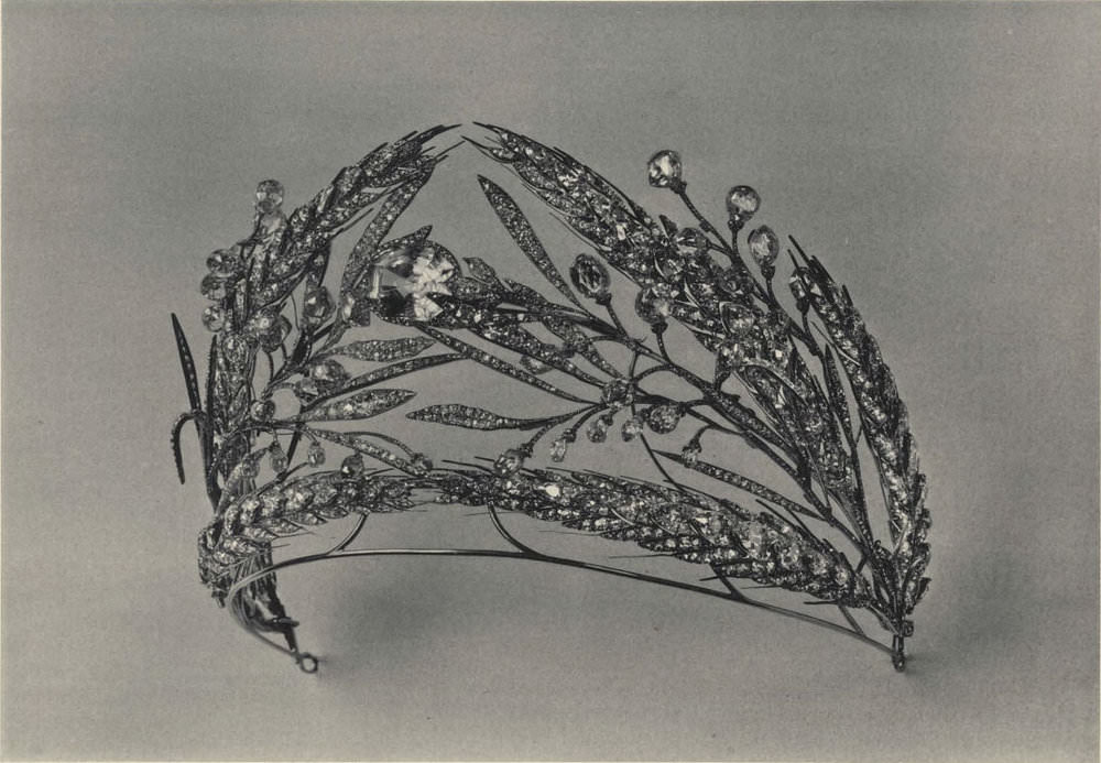 "Plate XXXI from the 1925 catalog. Regarding a viewing of this diadem in 1922 by the New York Times (from ""Avarice and Alienation""): ""This is the true wealth of Russia,"" said the head of the jewelry commission, ""not platinum, or diamonds wrung from the sweat of workers, but Russia's own natural grain—her noblest jewel."" Indeed, crown jewels cannot be eaten, and a month after this article appeared, a Times headline on September 21 warned that ""1,000,000 Face Starvation in Russia.""     The center stone in the diadem above is described in the 1925 catalog as a ""leuco-sapphire—very pure, yet somewhat cold-shaded of a yellow-wine tint, probably of Ceylon origin. ¶Weight (according to the ancient inv.)—37 a. c. ¶Dimensions: 2,1 x 1,7 x 1,5 cent."""