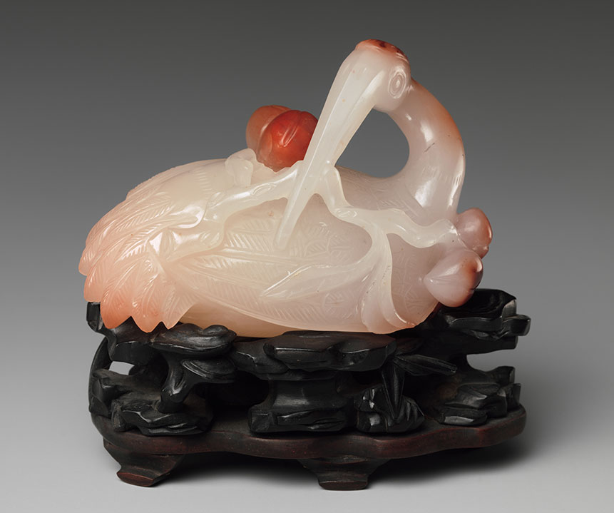 "Water Dropper in the Shape of a Crane.  Qing dynasty (1644–1911). Agate. Gift of Heber R. Bishop, 1902. 02.18.876. H. 2 3/8 in. (6 cm); W. 3 1/8 in. (7.9 cm). DP267509. ""A crane holding a branch of peaches symbolizes longevity,"" according to the  description  of this lovely carving. (Photo courtesy of The Met)"