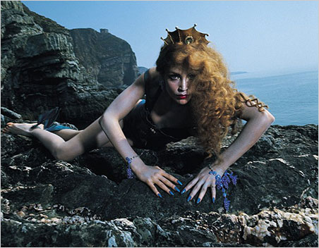Be brave, Ulysses.  From the  Siren  photo shoot, model Jerry Hall surveils. Bryan Ferry spotted the perfect location on television. It's at South Stack on the northwest coast of the island of Anglesey, off the northwest coast of Wales. Much of the isle's coastlands have been designated an Area of Outstanding Natural Beauty in the UK.