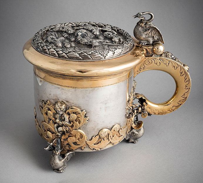 A lidded jug by early 18th-century silversmith Nathanael Heideman, made in Vyborg, one of the towns to which silver artisans would flee the next century. Swans decorate the vessel's three feet. (The whooper swan is Finland's national bird.) Each bird would have featured a chain and crown hanging from its beak as does the one atop the hinge. These designs seem to portray Bohun swans, which are derived from the legend of the Swan Knight. The pitcher cover's bas relief depicts an avian-helmeted soldier, sword raised, apparently restrained by a female monarch aided by attendants. All 'round are bearded goblin-y figures. At the queen's back stand three more figures, one of whom clutches his garment about his neck. (Photo © Ilari Järvinen)