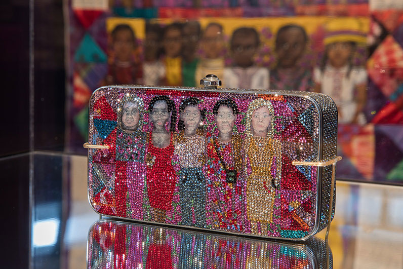 "Installation view of rhinestone-encrusted minaudière after Faith Ringgold's ""The Purple Quilt,"" 1986, with the original in the background. This and another clutch were collaborations with Ringgold to help the Guggenheim Museum to acquire one of the artist's story quilts. (Photo: Gary Mamay, courtesy the Leiber Collection)"