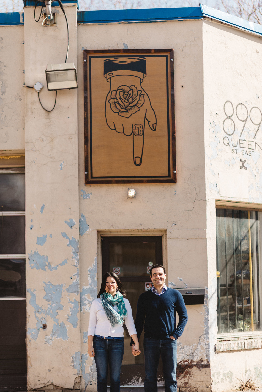 Creative shot of engaged couple below sign
