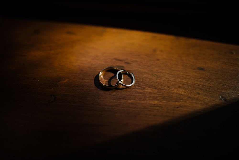 Detail shot of the wedding rings, dramatic and vintage