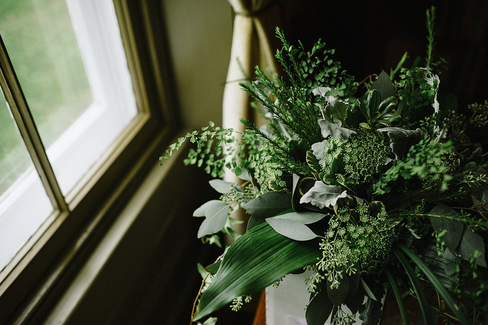 The bride's simple, green, wedding bouquet near the window wedding photography by Brian Batista Bettencourt of 3B Photography - Toronto's Best Wedding Photographer