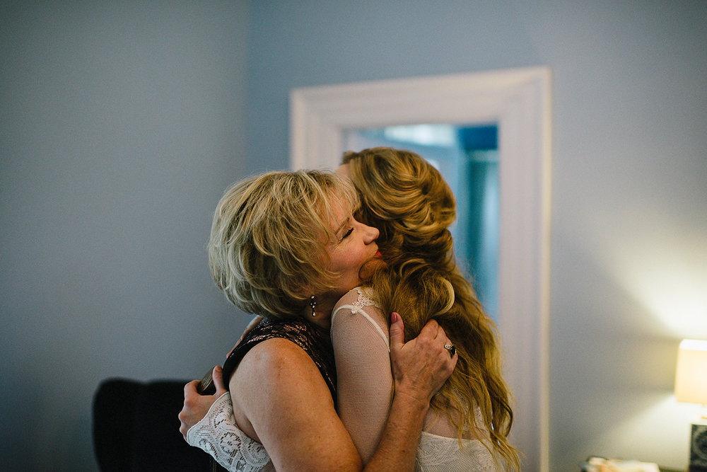 Best-Moody-Documentary-Wedding-Photography-Photojournalism-Vintage-Small-Town-Chapel-Wedding-Toronto-Ontario_Candid-Bride-and-mom-hugging.jpg