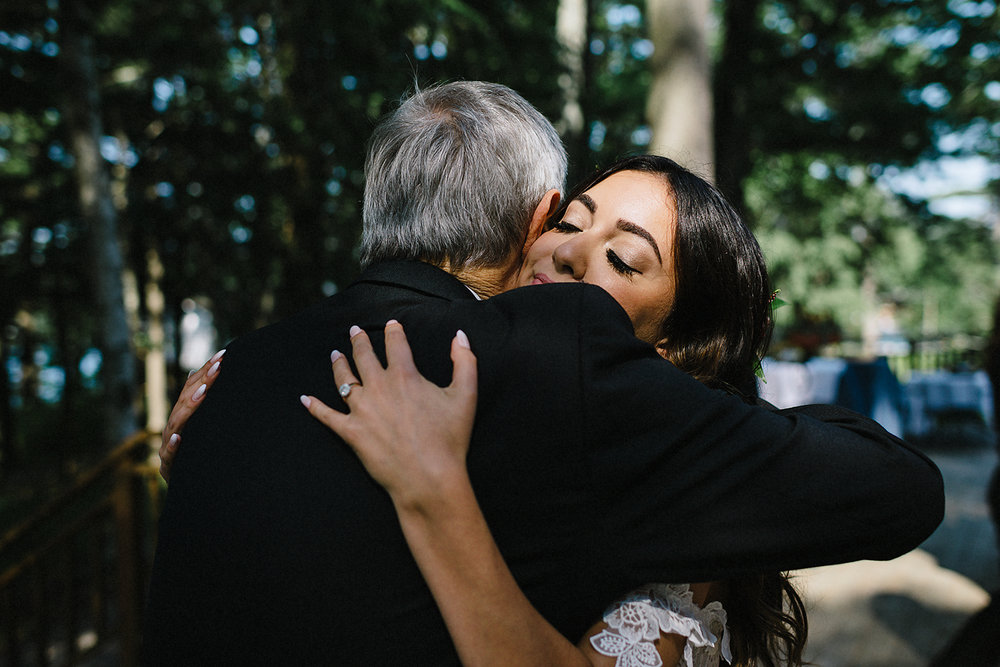Muskoka-Cottage-Wedding-Photography-Photographer_Photojournalistic-Documentary-Wedding-Photography_Vintage-Bride-Lovers-Land-Dress_Rue-Des-Seins_Forest-Reception-Candid-Guest-Hugging-Bride.jpg