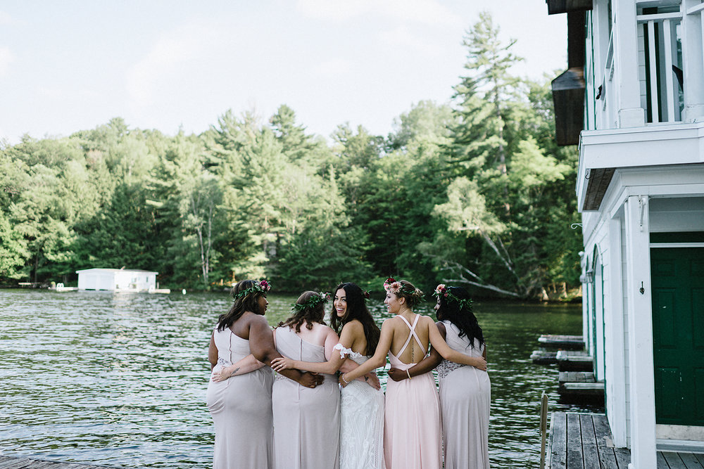 Muskoka-Cottage-Wedding-Photography-Photographer_Photojournalistic-Documentary-Wedding-Photography_Vintage-Bride-Lovers-Land-Dress_Rue-Des-Seins_Boho-Bride-and-bridal-party-hugging-by-lake.jpg