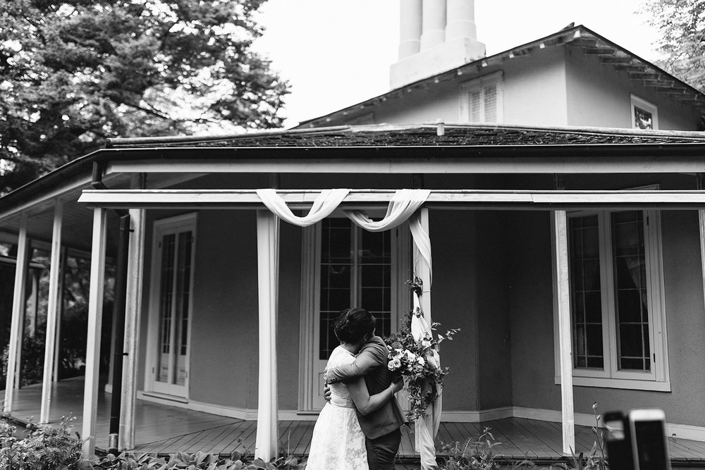 toronto-wedding-photographer-high-park-colborne-lodge-intimate-small-elopement-best-toronto-wedding-photographers-outdoor-ceremony-high-park-cherry-blossoms-bride-and-groom-vows-love-love-first-kiss-hugging-just-married-bw.jpg