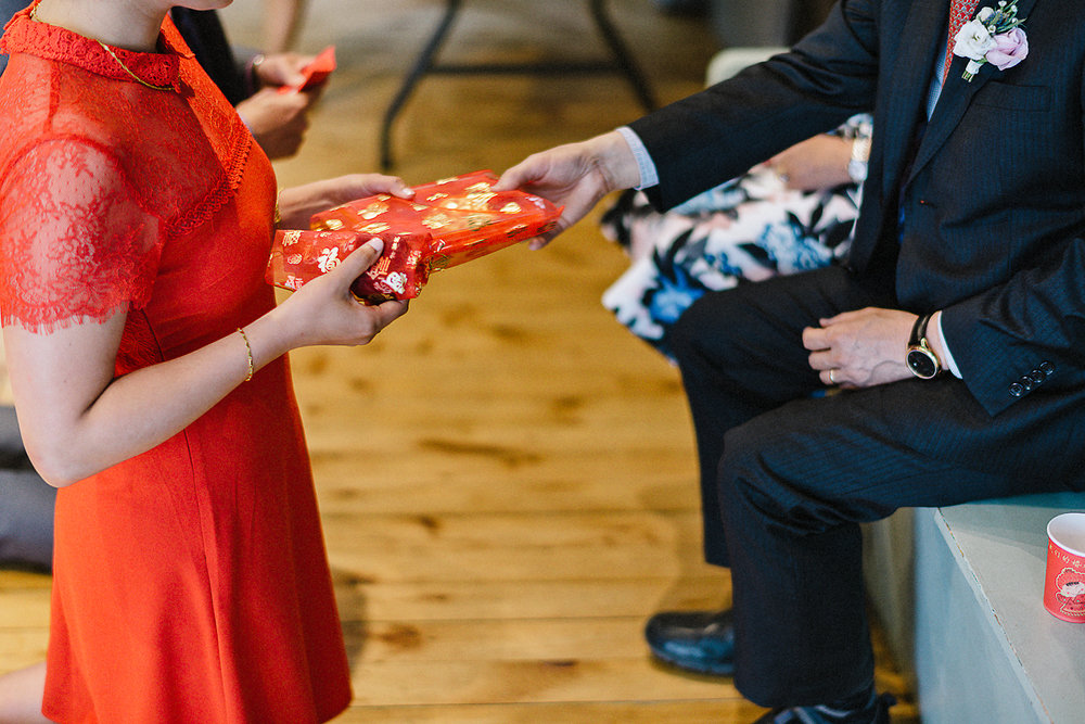 Chinese-Tea-Ceremony-in-outdoor-forest-venue-toronto-high-park-colbourn-lodge-dog-friendly-venue-bride-and-groom-candid-moment-best-documentary-wedding-photographers-Chinese-Tea-Ceremony-Gift-Giving-DEtail-REd-Colour-palette.jpg