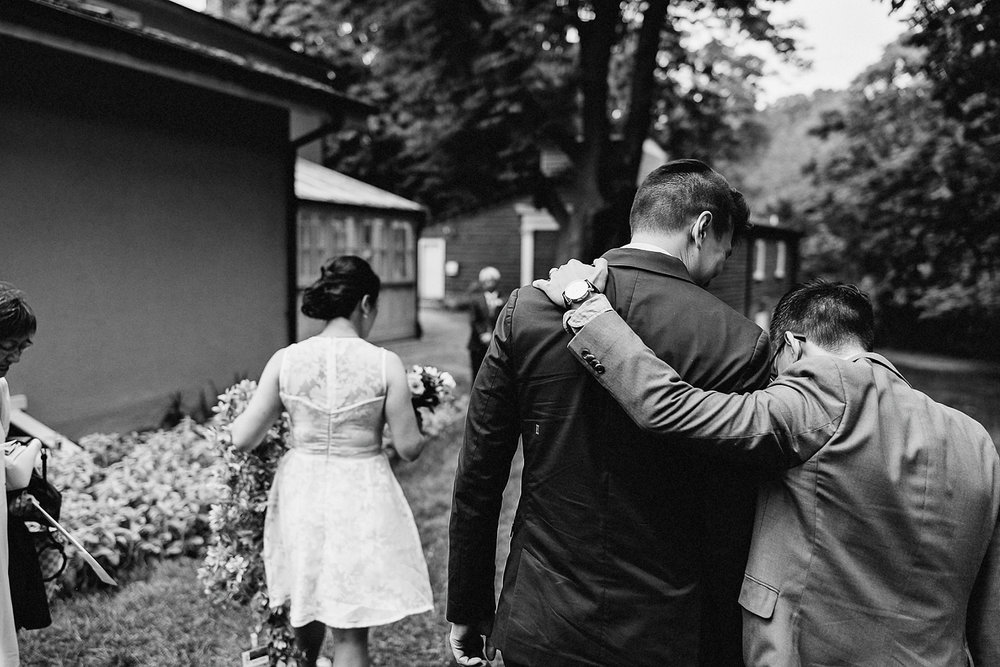 Outdoor-CeremonyIdeas-Bride-and-Groom-Exit-Toronto-Vintage-Bride-Outdoor-Forest-Wedding-Venue-High-Park-Downtown-Toronto_Candid-Editorial-Documentary-Wedding-Photographers-Sweet-Candid-Moment-Between-Groom-and-Brother.jpg