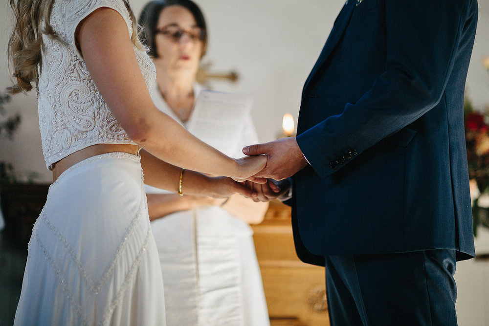 best-toronto-wedding-photography-3b-photography-kleinberg-small-chapel-wedding-intimate-gta-toronto-ontario-ceremony-alter-details-florals-by-hunt-and-gather-bride-and-groom-saying-vows-holding-hands.jpeg