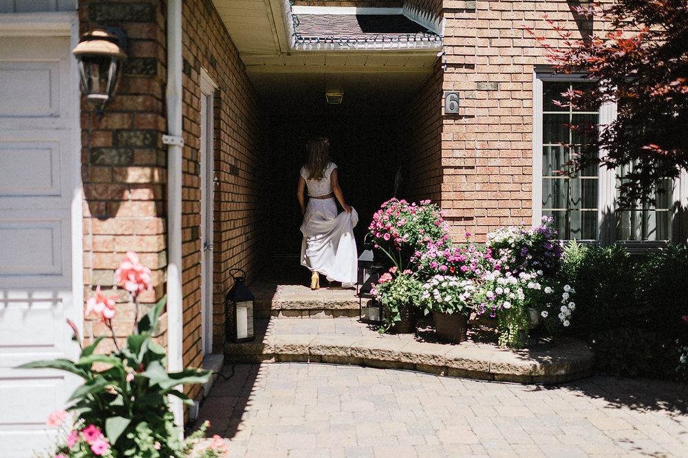 Boho-Bride-Aesthetic-Loversland-Two-Piece-Wedding-Dress-Bo-and-Luca-Isra-Dress-Summer-Wedding-Doctors-House-Best-Toronto-Wedding-Photographers-Vintage-Wedding-Portrait-of-Bride-Soft-Portraiture-Fine-Art-Documentary-Portrait-in-front-of-house.jpg