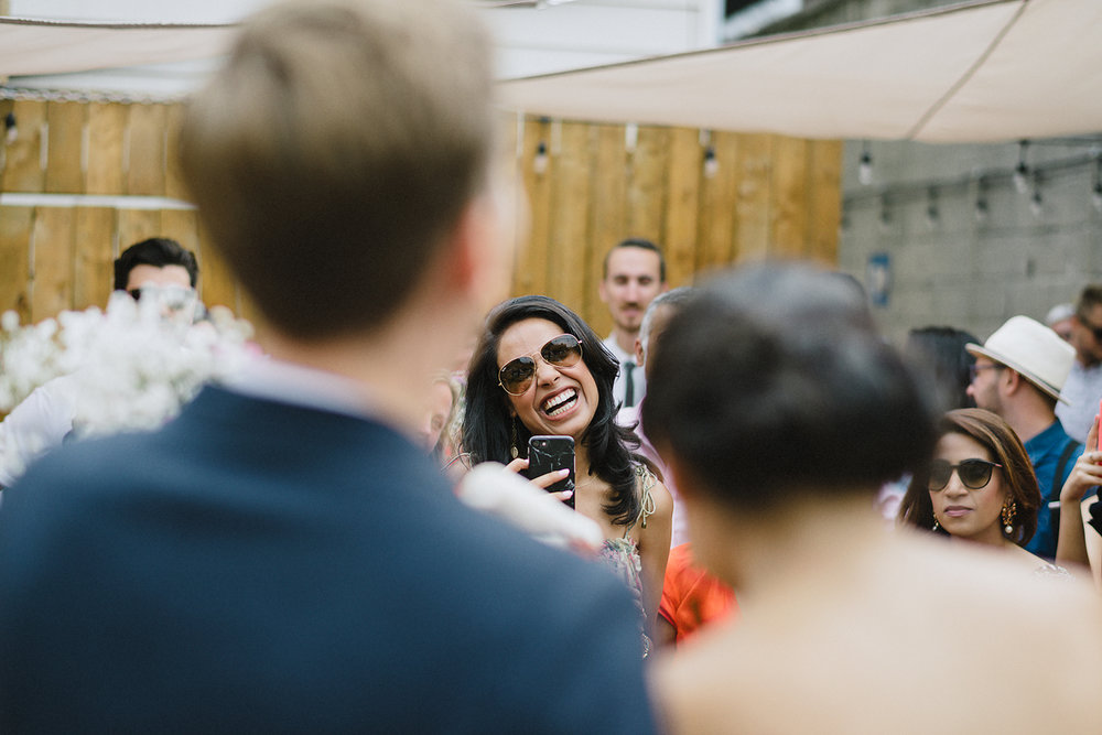 film-analog-photography-toronto-film-wedding-photographers-alternative-reception-bar-pray-tell-cocktail-hour-reception-on-the-patio-casual-bride-and-groom-hugging-guests-smiling-iphone-photo.jpg