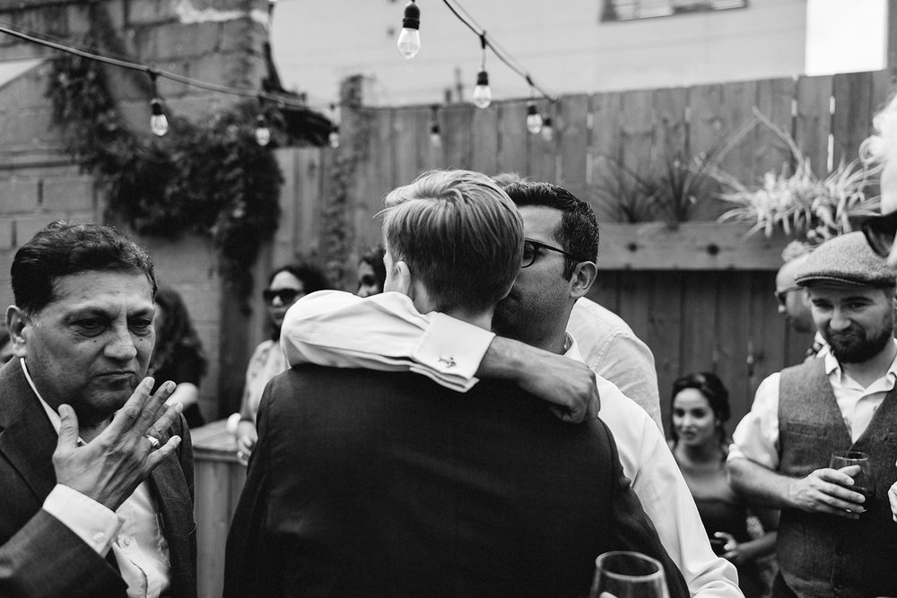 film-analog-photography-toronto-film-wedding-photographers-alternative-reception-bar-pray-tell-cocktail-hour-reception-on-the-patio-casual-bride-and-groom-hugging-guests-smiling-happy-celebrating-family-brother.jpg